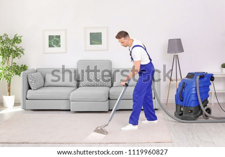 Male worker removing dirt from carpet with professional vacuum cleaner indoors #1119960827