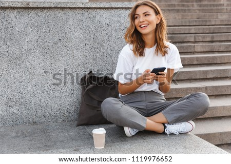 Image of beautiful stylish woman sitting on street stairs with legs crossed on summer day and holding mobile phone #1119976652