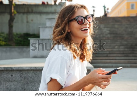 Picture of european brunette woman wearing casual summer outfit and sunglasses laughing while walking through city street with smartphone in hands #1119976664