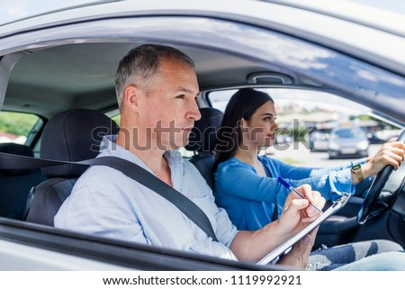 Young woman on a driving test with her instructor. Learning to drive a car. Driving school. Instructor of driving school giving exam while sitting in car #1119992921