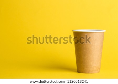 coffee to go in a disposable cup on a yellow background, place for text #1120018241