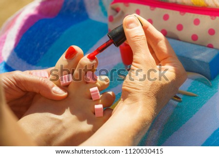 Woman relaxing doing her pedicure with red nail polish on beach towel. Female taking care of feet #1120030415