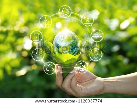 Hand holding light bulb against nature on green leaf with icons energy sources for renewable, sustainable development. Ecology concept. Elements of this image furnished by NASA. Royalty-Free Stock Photo #1120037774