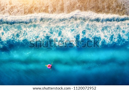 Aerial view of woman swimming on the pink swim ring in the transparent sea and beautiful waves in Europe. Summer landscape with girl, beach, blue water at sunset. Top view. Travel and holiday. Resort #1120072952