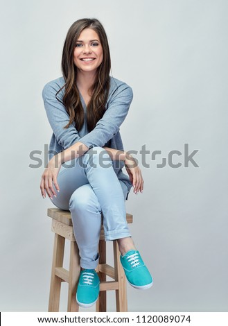 Smiling young woman sitting on stool with crossed legs. Isolated studio portrait on gray back. #1120089074