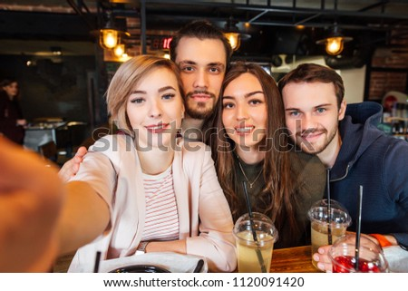 Group of smiling friends taking selfie in loft bar. People, leisure, friendship and technology concept