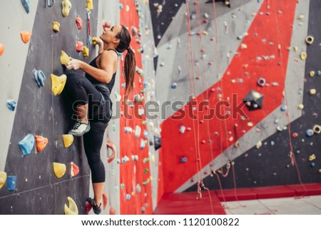 Rear view of sportwoman climber moving up on steep rock, climbing on artificial wall indoors. Extreme sports and bouldering concept. Royalty-Free Stock Photo #1120100822