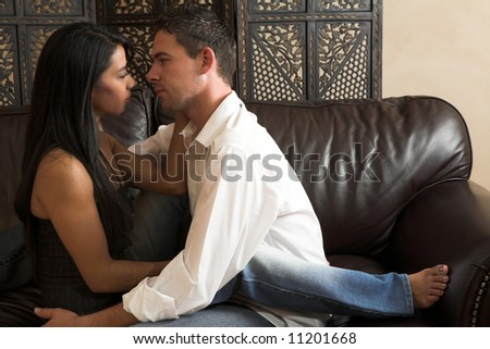 Multi-ethnic couple in passionate embrace and undressing each other during sexual foreplay #11201668