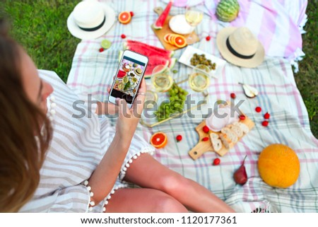 Young girl making food photo at summer picnic
