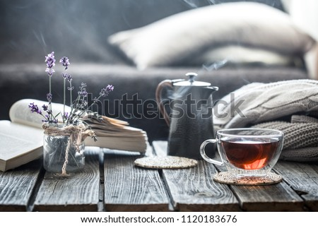still life book and a cup of tea in the living room on a wooden table, the concept of coziness and interior Royalty-Free Stock Photo #1120183676