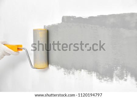 Painting white wall in grey color with roller brush #1120194797