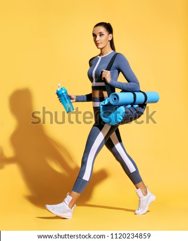 Go to gym! Attractive latin woman in fashionable sportswear on yellow background. Dynamic movement. Side view. Sports and healthy lifestyle #1120234859