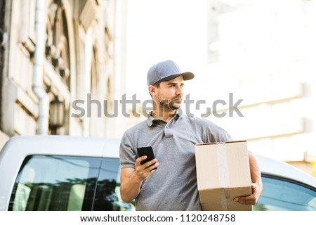 your shipping is here. delivery man in grey shirt with cap standing with his cardboard box on the street using his mobile phone, in front of his car outside on the street #1120248758