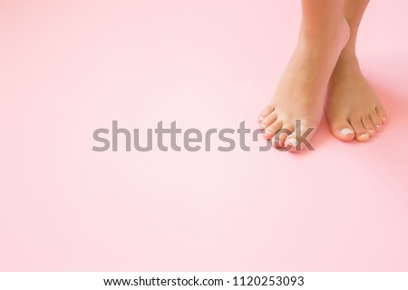 Young, perfect groomed woman's feet on pastel pink background. Care about nails and clean, soft, smooth body skin. Pedicure and manicure beauty salon. Copy space. Empty place for text or logo. #1120253093