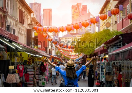 Young woman traveler with backpack and hat traveling into Chinatown at singapore city downtown. Travelling in Singapore concept #1120335881