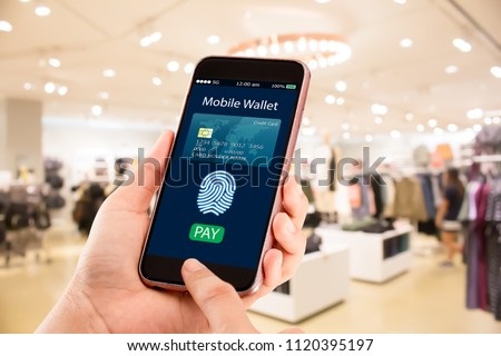 Digital mobile wallet concept.Hands holding mobile phone on blurred fashion store as background #1120395197