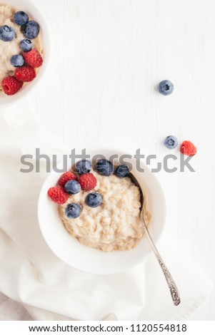 A bowl of oatmeal porridge with blueberries and raspberries on white wooden table. Top view. #1120554818