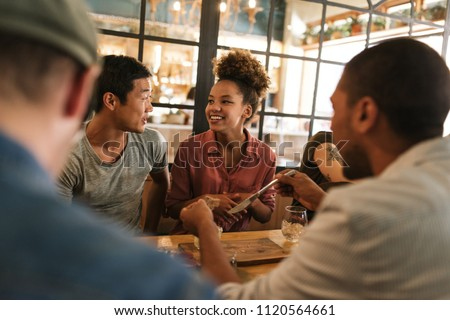 Diverse group of smiling young friends sitting at a table in a bistro talking together over a meal #1120564661