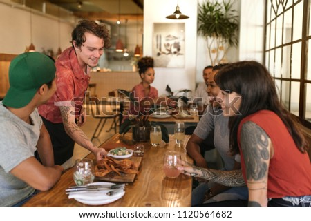 Friendly waiter serving delicious freshly made tapas to a group of laughing customers sitting at a table in a bistro #1120564682