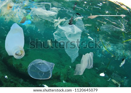 Plastic ocean pollution. Underwater bags, bottles, cups, straws and ear buds     Royalty-Free Stock Photo #1120645079
