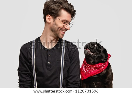 People and animals concept. Friendly looking handsome male looks postively at his favourite dog, pose for magazine photo, enjoy time together, isolated over white background. Man pet lover has joy