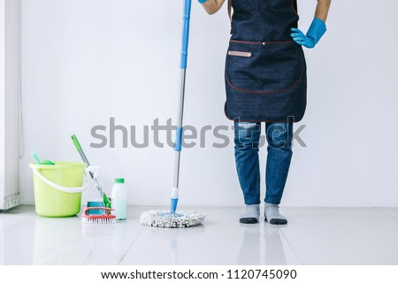 Housekeeping and cleaning concept, Happy young woman in blue rubber gloves wiping dust using mop while cleaning on floor at home. #1120745090