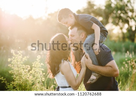 Happy young family spending time together outside in green nature on vacation outdoors. The concept of family holiday.