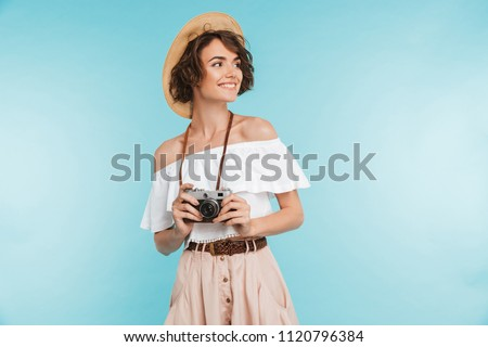 Portrait of a smiling young woman in summer hat standing with photo camera and looking away at copy space isolated over blue background #1120796384