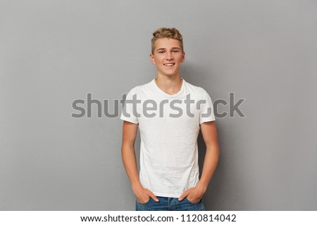 Portrait of a smiling relaxed teenage boy looking at camera while standing over gray background #1120814042