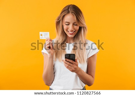 Portrait of a happy young blonde girl showing plastic credit card while using mobile phone isolated over yellow background #1120827566