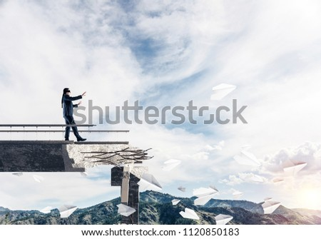 Businessman walking blindfolded on concrete bridge with huge gap as symbol of hidden threats and risks. Skyscape and nature view on background. 3D rendering. #1120850183
