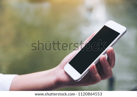Mockup image of a woman holding white smart phone with blank black desktop screen with blur green nature background #1120864553