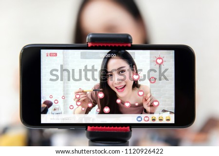 Asian woman professional beauty vlogger or blogger live broadcasting cosmetic makeup tutorial viral video clip by smartphone sharing on social media #1120926422