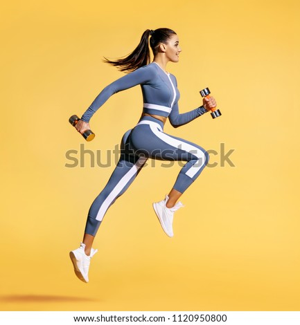 Sporty woman jumping with dumbbells. Photo of active woman in sportswear on yellow background. Dynamic movement. Side view. Sport and healthy lifestyle #1120950800