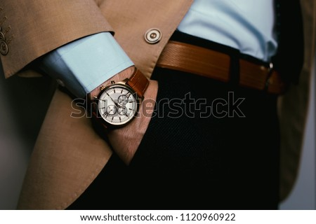 Closeup fashion image of luxury brown  watch on wrist of man.body detail of a business man.Man's hand in pants pocket closeup at white background.Man wearing beige jacket and white shirt.Not isolated #1120960922