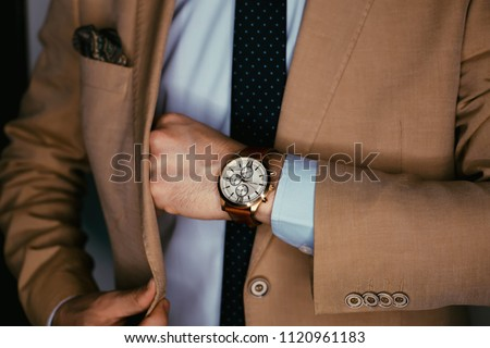 Businessman luxury style. Men style.correct button on jacket, hands close-up, dressing, man's style, stylish man.Fashion portrait of young businessman handsome model man in casual cloth suit. #1120961183