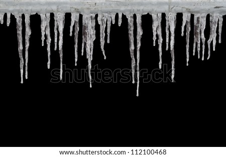 Row of long icicles on black background Royalty-Free Stock Photo #112100468