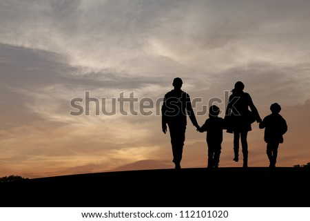 Silhouette of a family comprising a father, mother and two children walking into the sunset.