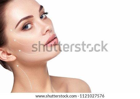 portrait of beautiful woman with perfect skin of the face, with arrows on face, concept of lifting skin. Cosmetology, elastic and young skin of the face. #1121027576