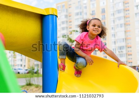 happy african american little kid sliding down from hill at playground  #1121032793