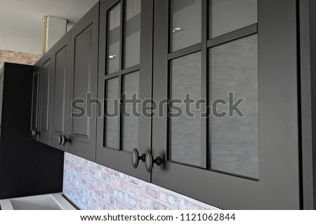 Black handles vintage style on black kitchen wooden cabinets  Royalty-Free Stock Photo #1121062844