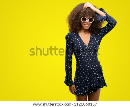 African american woman with sunglasses and summer dress stressed with hand on head, shocked with shame and surprise face, angry and frustrated. Fear and upset for mistake. #1121068157