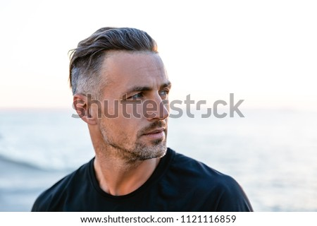 close-up portrait of handsome adult man with grey hair looking away on seashore Royalty-Free Stock Photo #1121116859