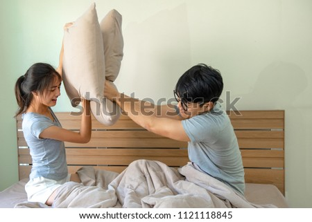Asian young couple having pillow fight together on bed. #1121118845