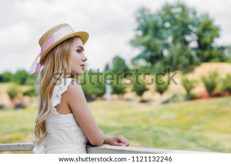 pensive attractive blonde girl in wicker hat with ribbon leaning at railing and looking away outdoors #1121132246