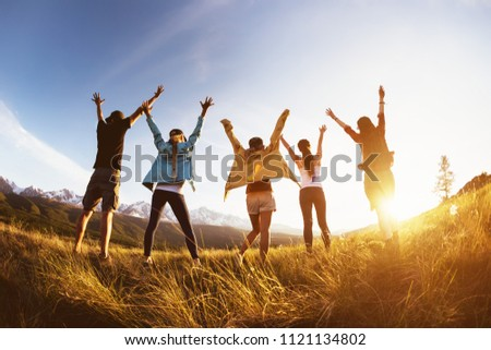 Group of happy friends stands against mountains sunset with raised arms and having fun #1121134802