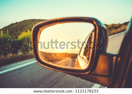 Beautiful sunset in sideview car mirror on mountain road #1121178233