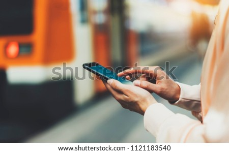 blogger hipster using in hands gadget mobile phone, woman texting message on blank screen smartphone, mockup online wifi internet concept, hipster waiting on station platform on background train #1121183540