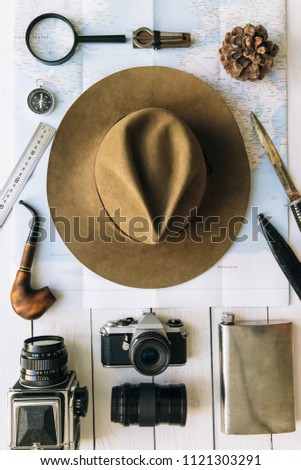 Adventure planning flat lay. Travel vintage gear on map. Including film camera, hat, knife, loupe, compass. Exploring, hiking empty space poster, postcard concept.