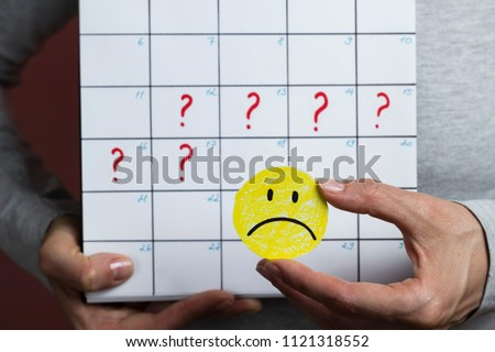Delay of menstruation, violation of the menstrual cycle. The girl is holding a sad smiley on the background of the calendar period. Royalty-Free Stock Photo #1121318552